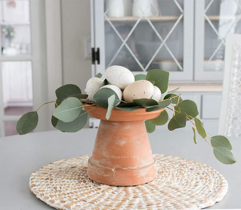 terra cotta pot with eggs and greenery on table
