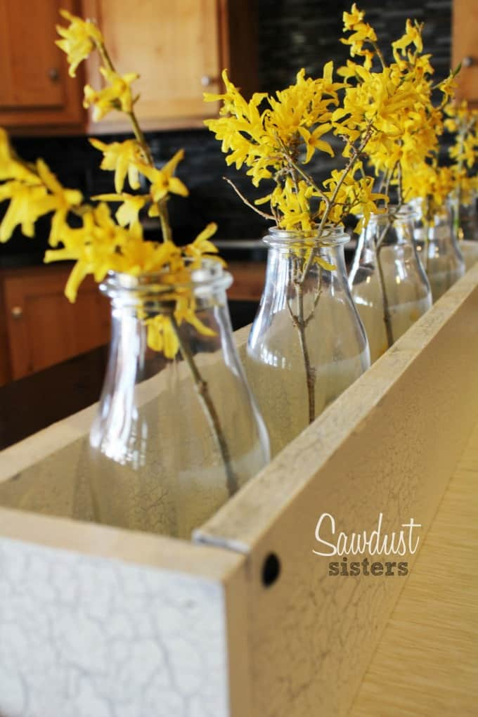 easy and lovely spring centerpieces wooden box with forsythia in milk bottles