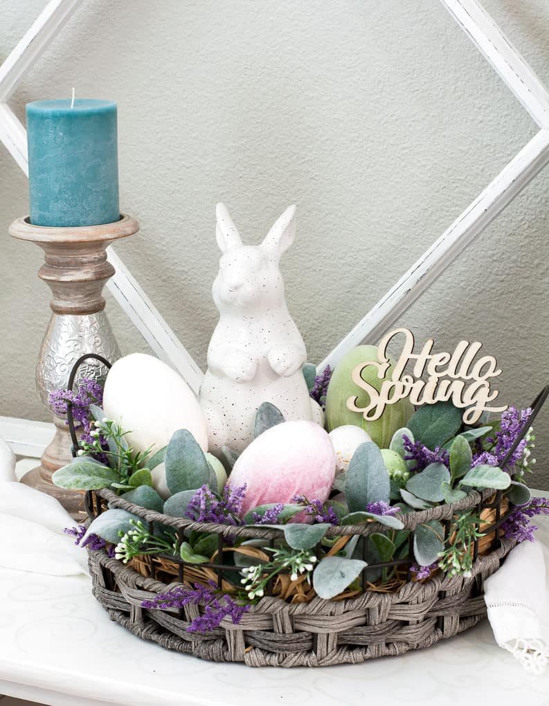easy and lovely spring centerpieces white bunny in basket with florals and velvet eggs with candlestick and windowpane in background