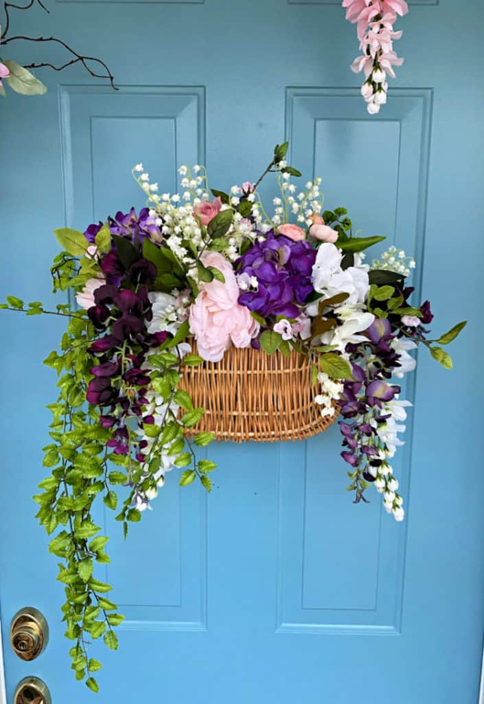 basket with overflowing florals on blue door