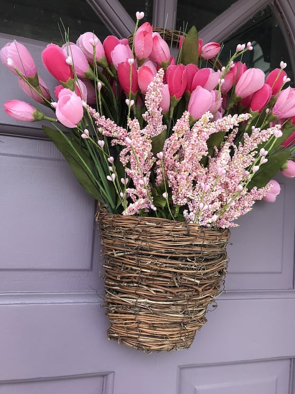 grapevine basket with pink tulips and greenery on purple door