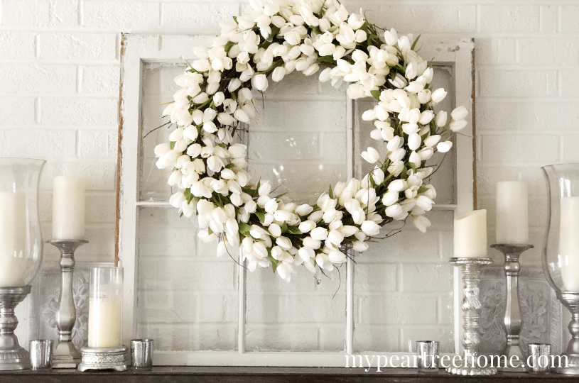 white tulip wreath on windowpane set on mantel