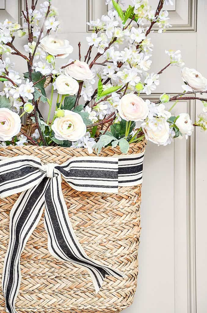 basket with white and green florals with black and white ribbon on door