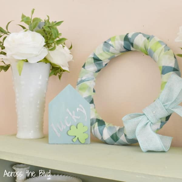 tuesday turn about 38 vignette with wreath flower vase and wooden sign on shelf