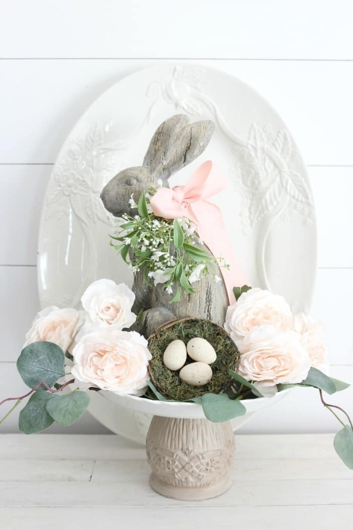 cake stand on wood surface with bunny flowers and white platter