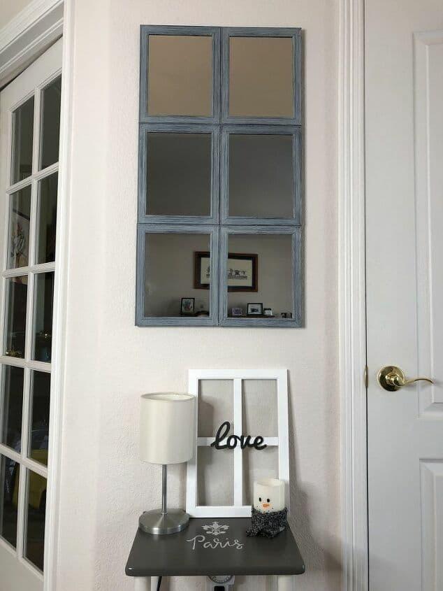 windowpane mirror on wall with decor below