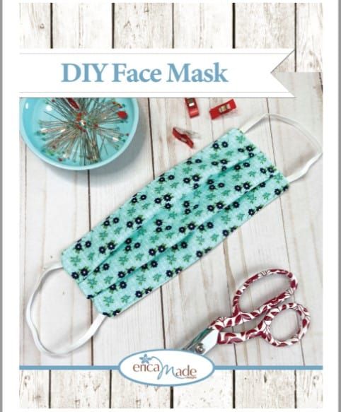 face mask with sewing items on wood surface
