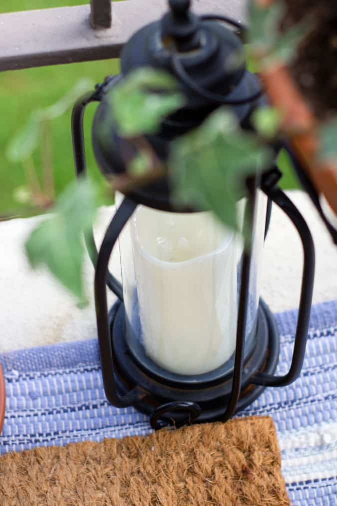 black lantern with white candle sitting on blue rug