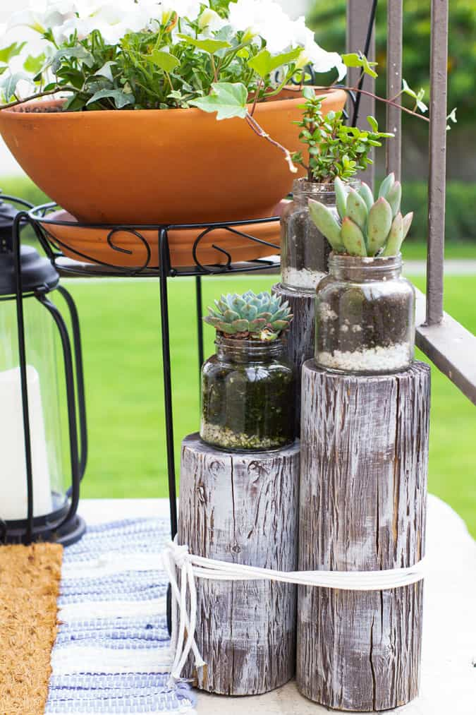 wood pilings with succulent jars on tiny patio space
