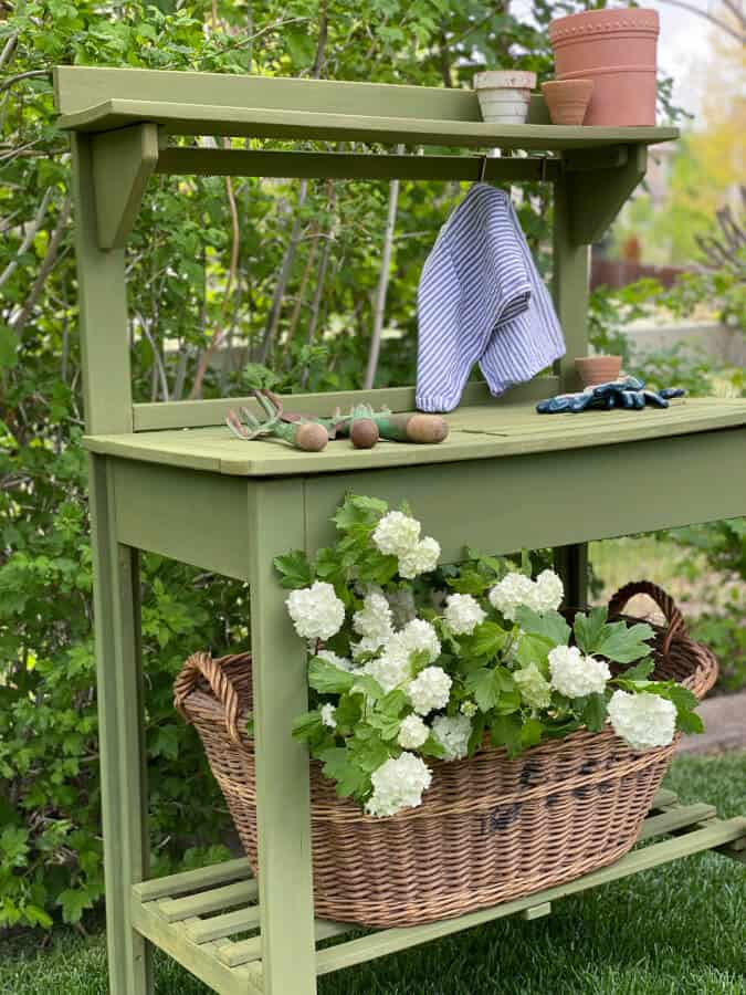 green potting bench with hydrangeas and potting tools in garden