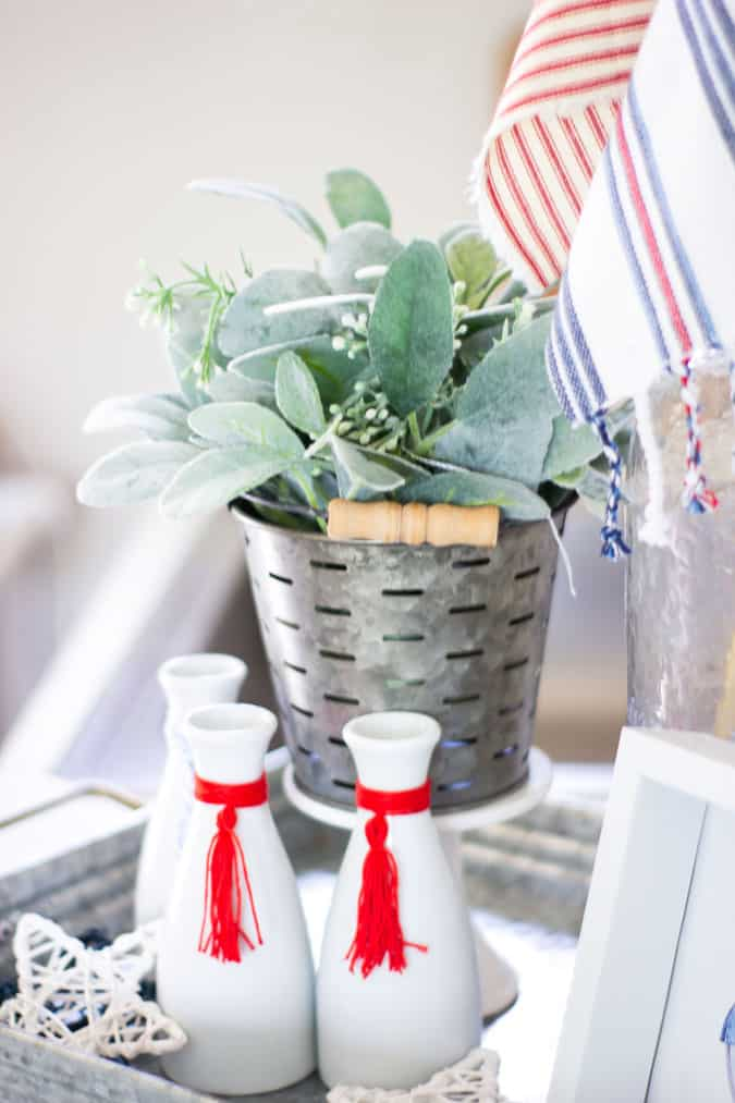 understated patriotic vignette with olive bucket and greenery and white bottles