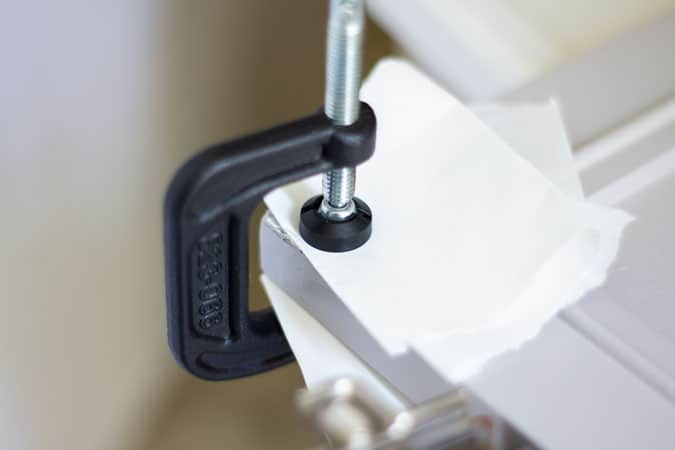 c-clamp with paper clamped on cabinet door