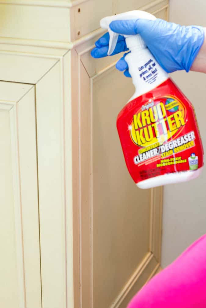prepare cabinets for paint yellow cupboards sprayed with krud kutter with gloved hand