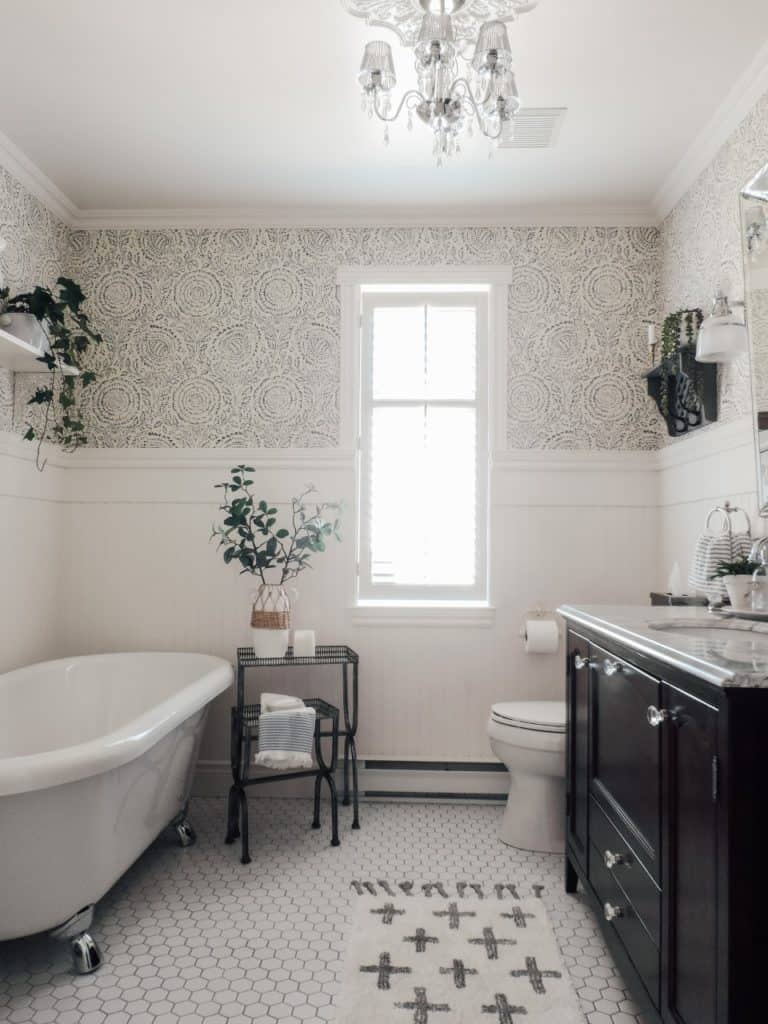 white and gray bathroom with clawfoot tub black vanity and decor