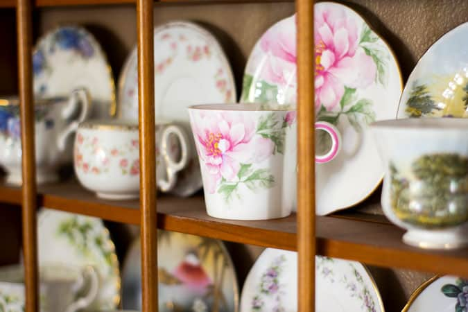 floral teacup and saucer on teacup rack
