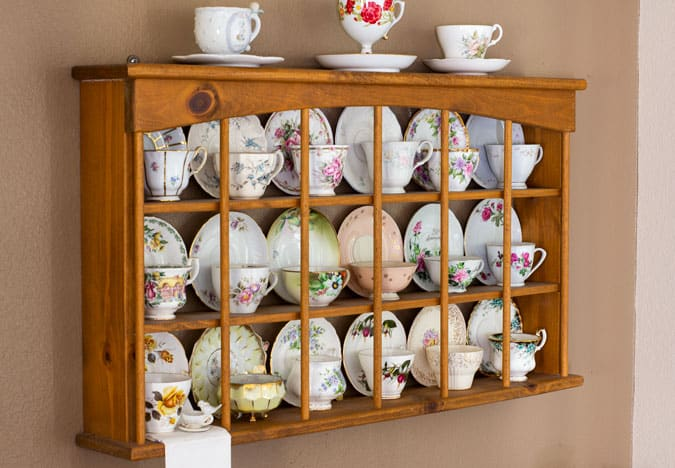 so cal traveling teacup on teacup shelf with other teacups on wall