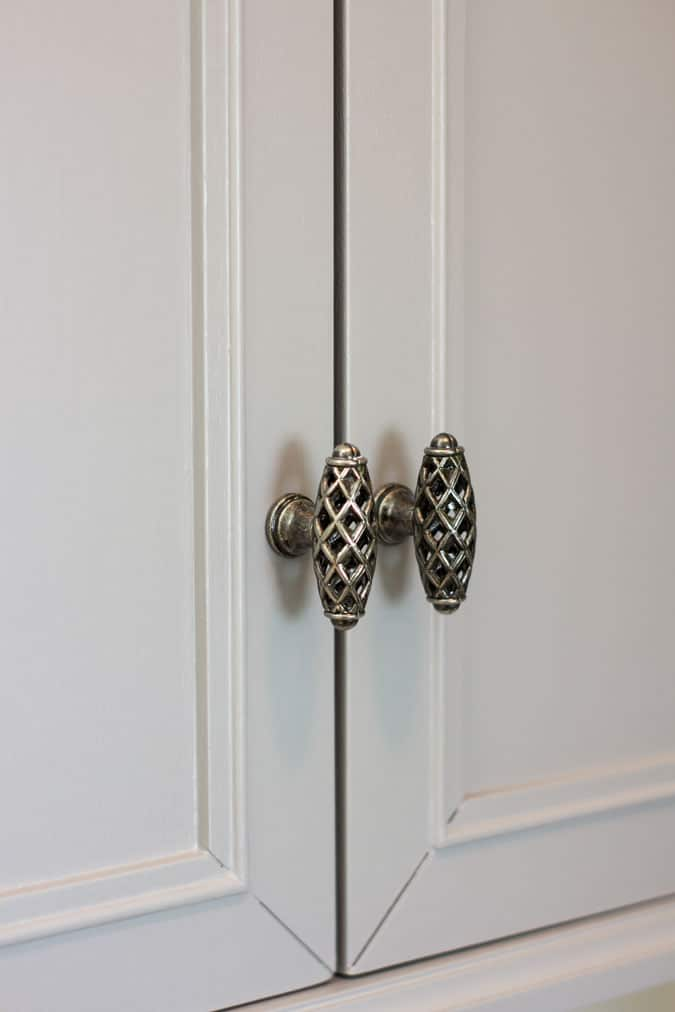 gray cabinet with silver filigree hardware