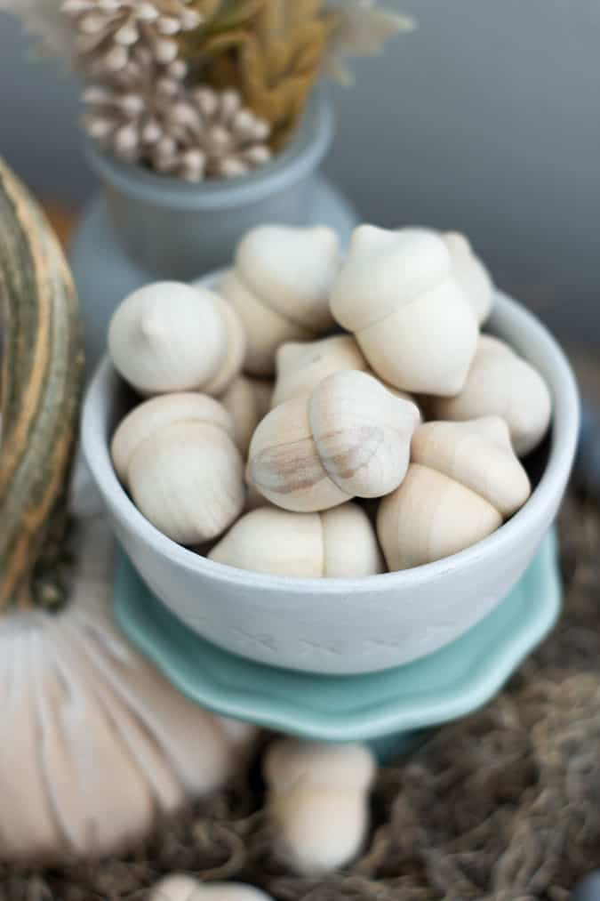 bowl of wooden acorns on a green stand