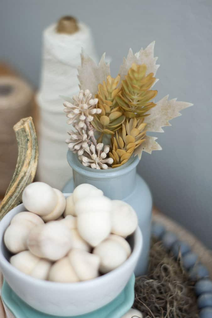 neutral fall cloche with pumpkin floral vase moss and bowl of wooden acorns and vase with fall florals