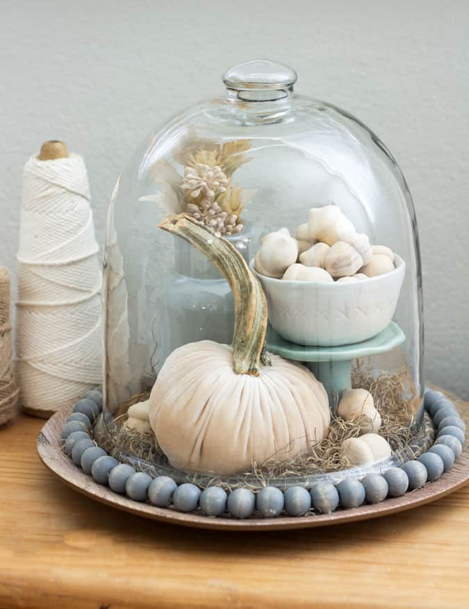 neutral fall cloche with pumpkin floral vase moss and bowl of wooden acorns