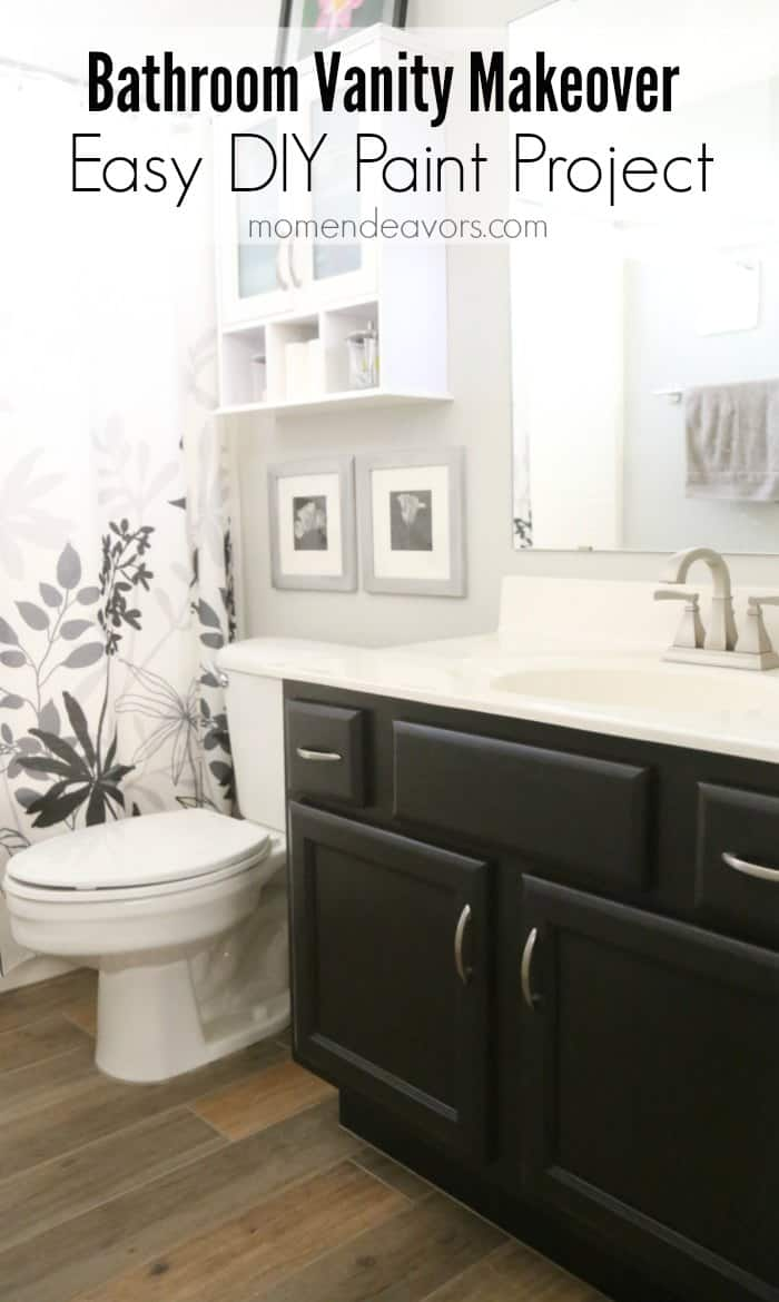 black vanity in white bathroom with silver accents