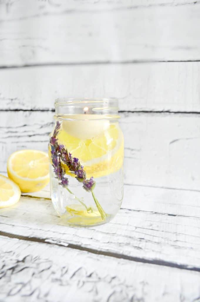 mason jar with lemons lavender and tealight on wood background