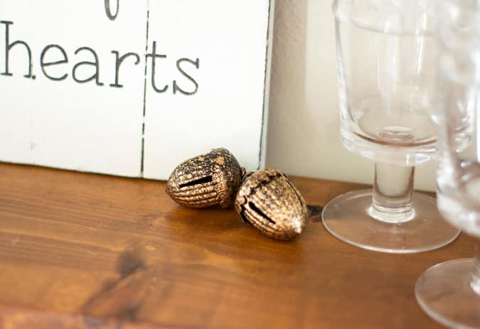 copper jingle bell acorns on wood shelf