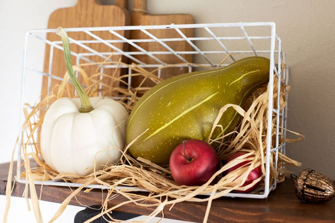 wire basket with fall produce and raffia on shelf with cutting boards in background