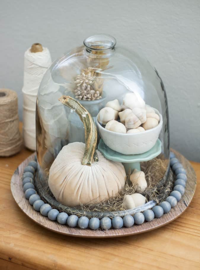 charger with wood beads and fall elements under a cloche on wood surface