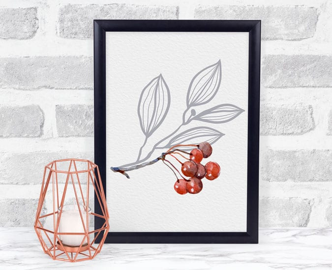 print of berries with gray leaves in black frame with candle on white surface