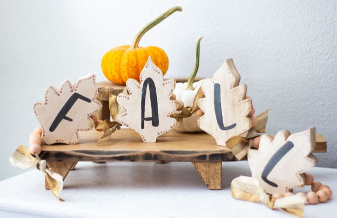 fall wood leaf garland on bread board with pumpkin in background