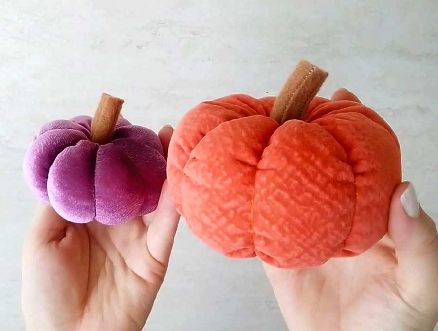 purple and orange pumpkins being held in womans hand