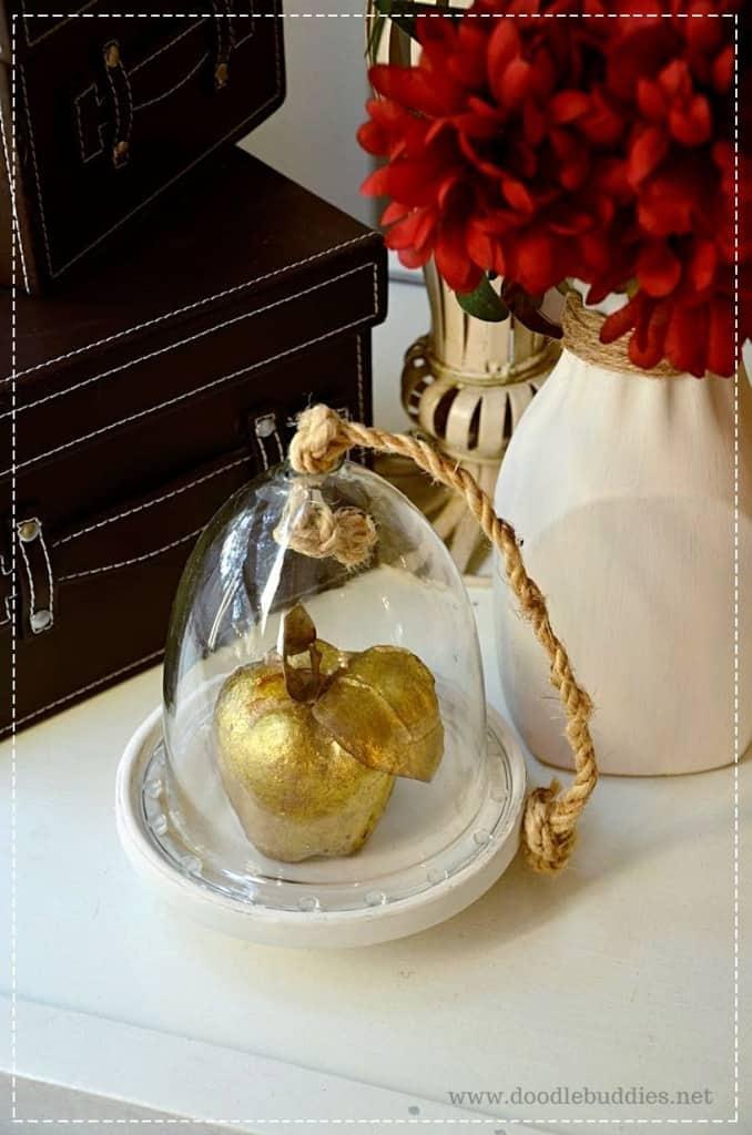 bell jar cloche with a golden apple