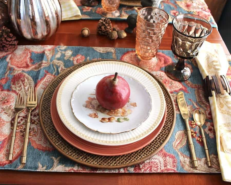tablesetting with fall colors and a red pear on a tapestry placemat