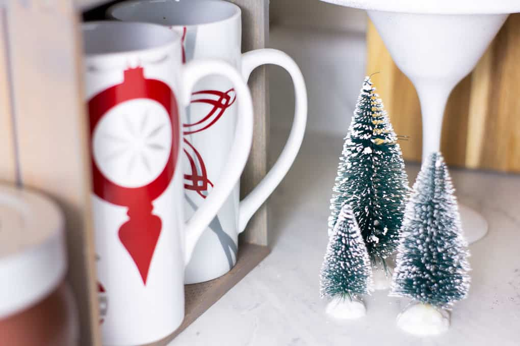 christmas coffee mugs and bottle brush trees on white surface