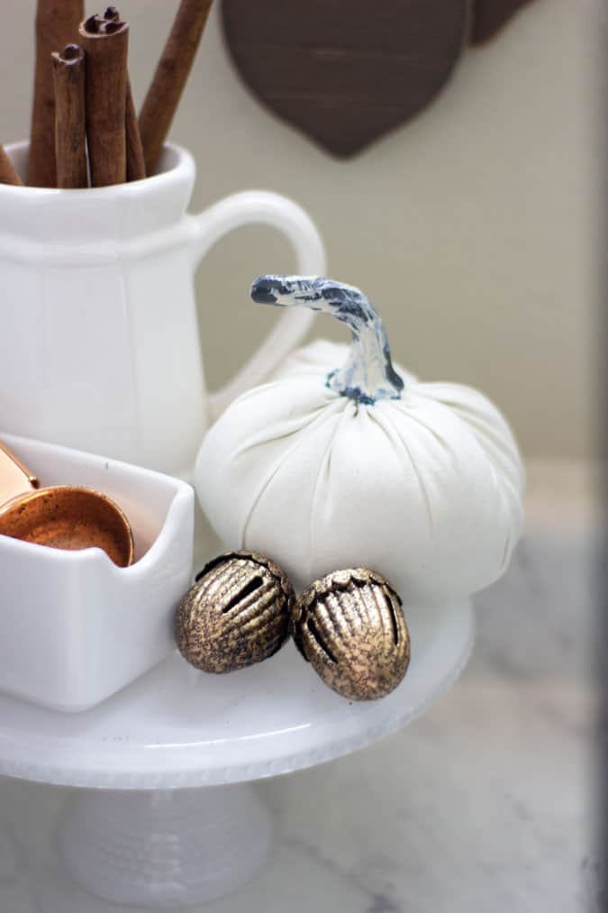 metal acorns and fabric pumpkin on cake plate