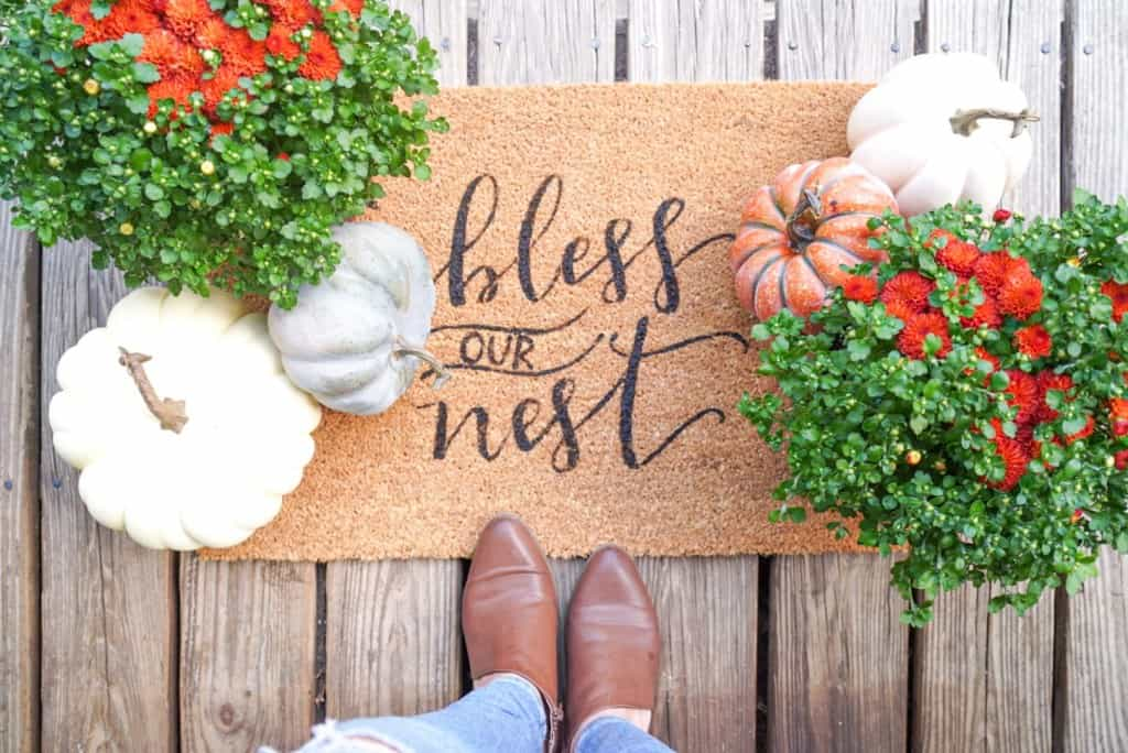 stenciled mat on outdoor porch with florals pumpkins and booted feet