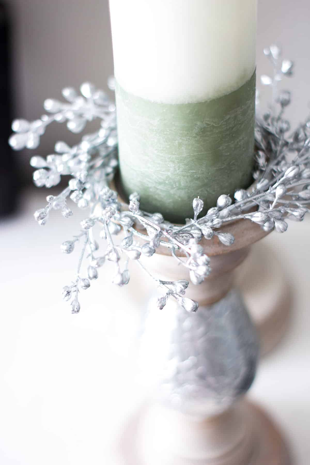 silver seeded candle ring on pillar holder with white green candle