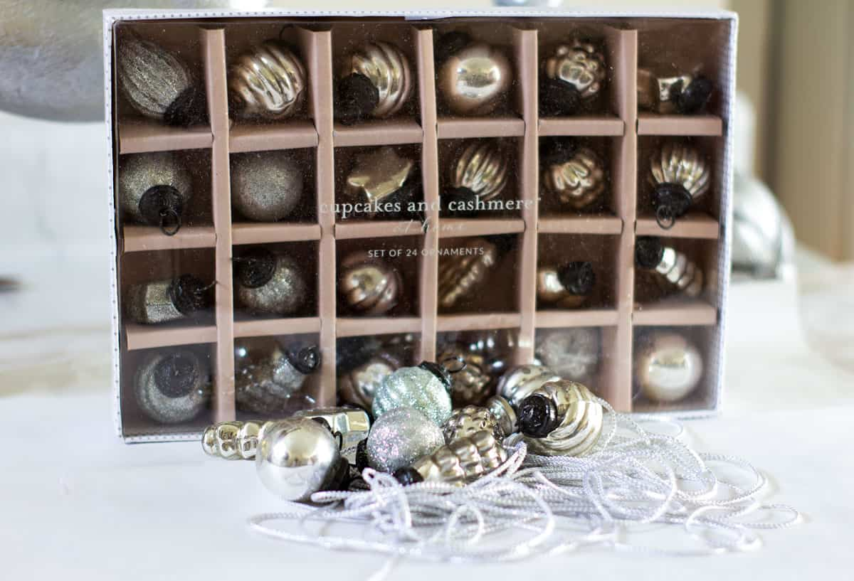 mercury glass ornaments in a box and on the counter with sparkly twine