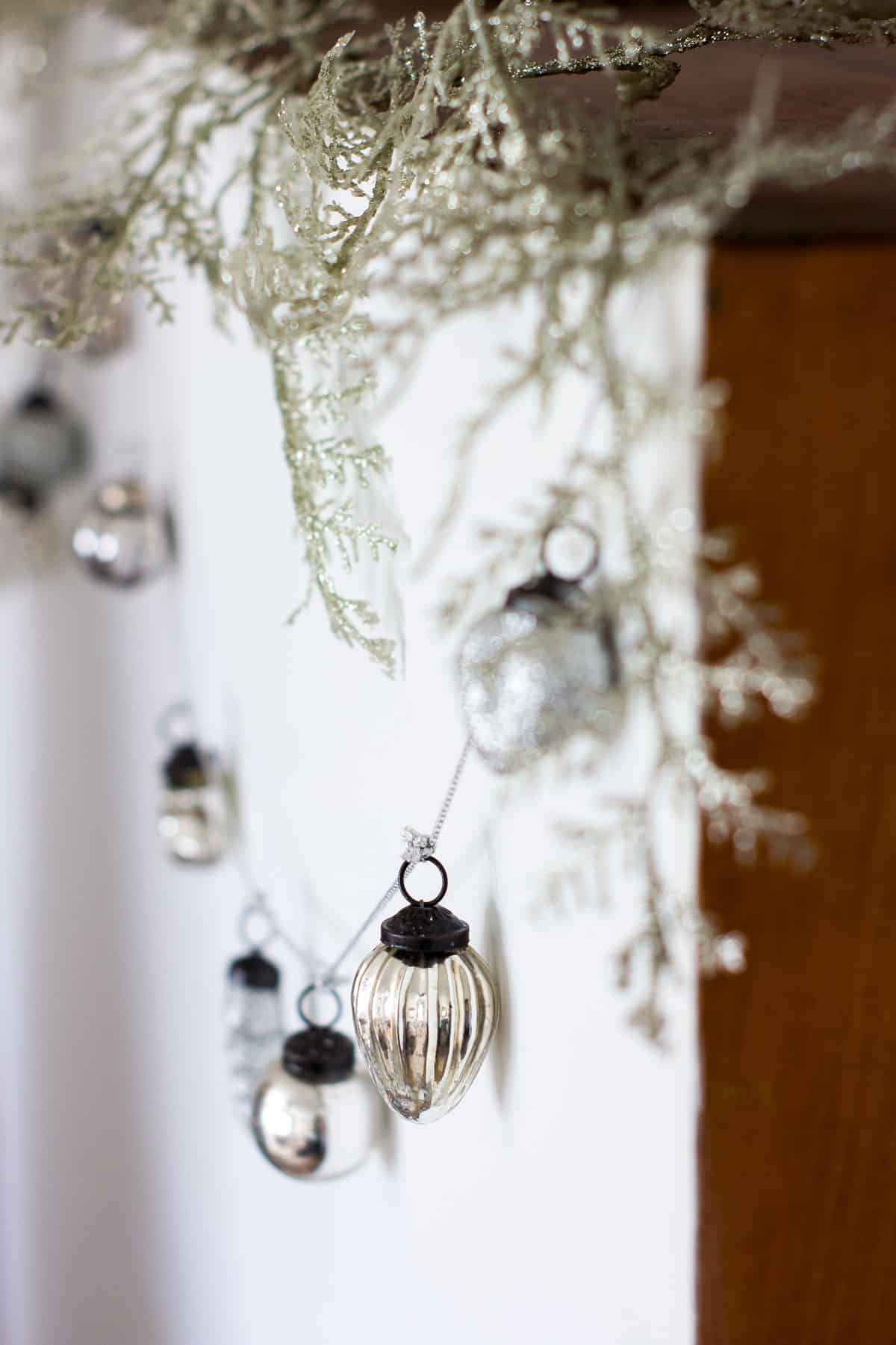 mercury glass ornament garland hanging on back of hutch with sparkly branches