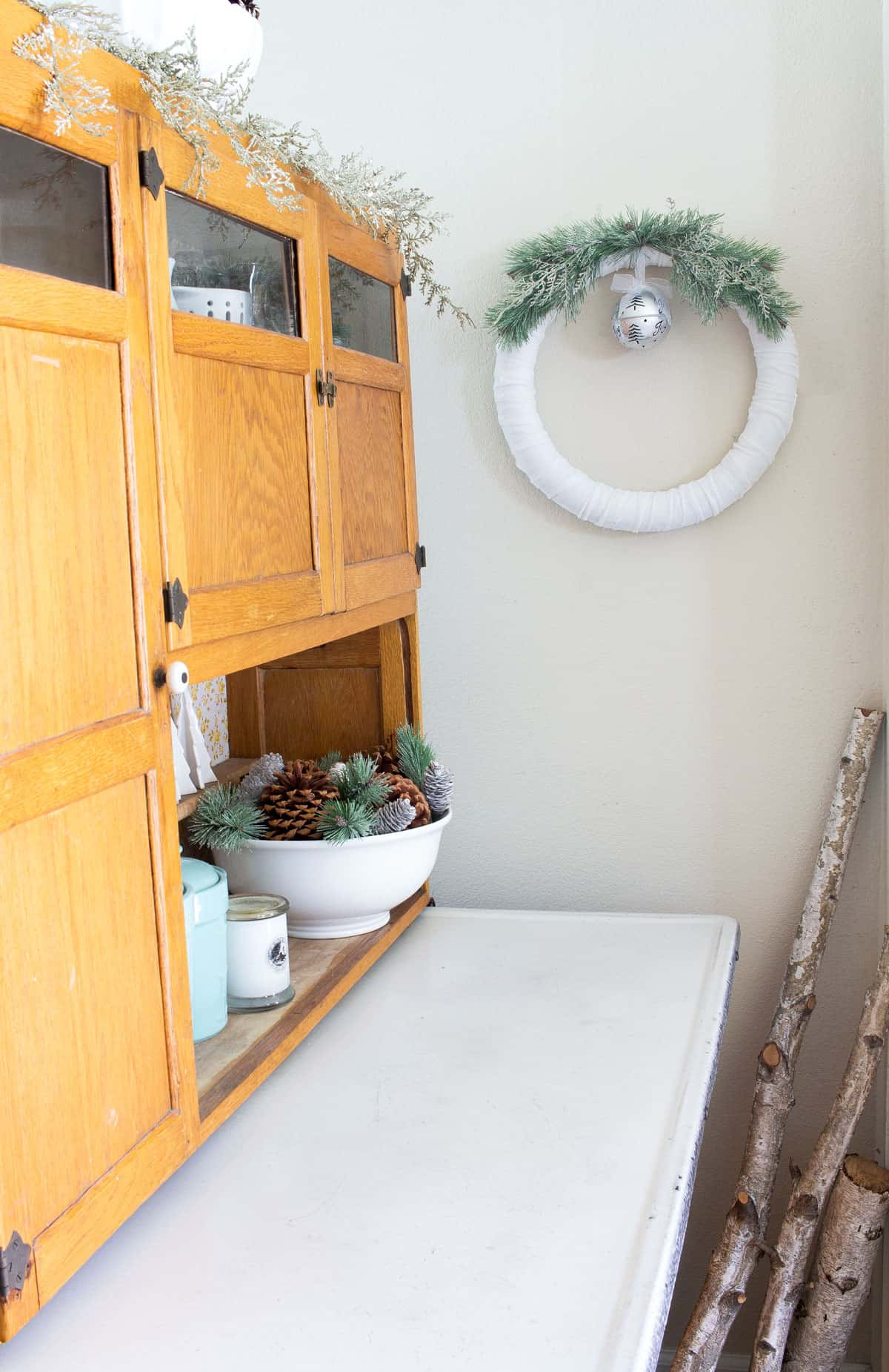 frosty velvet christmas wreath next to a bakers cabinet