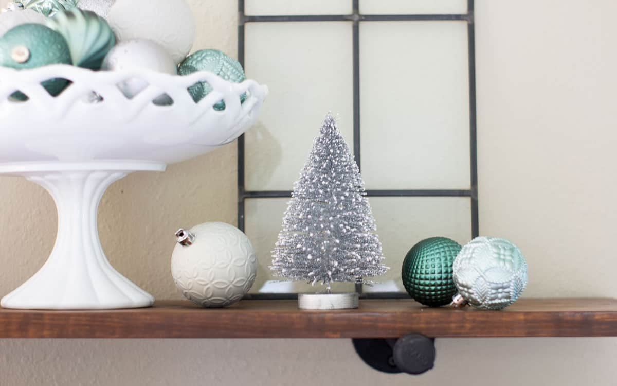 open shelf with green gray and white christmas ornaments and bottle brush tree