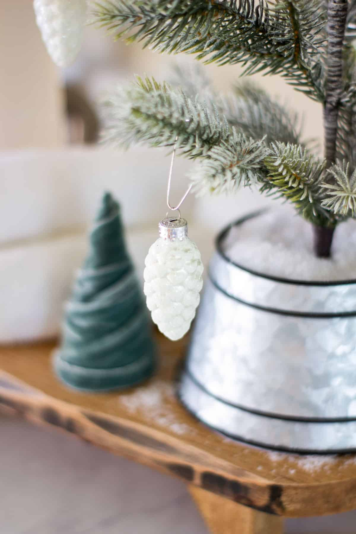 white pinecone ornament on tree with velvet tree in background