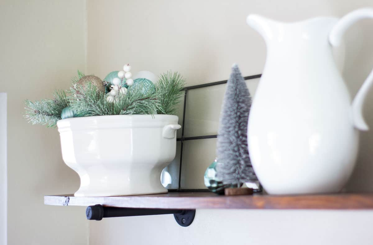 frosty christmas tiny home touropen shelf with green gray and white christmas ornaments and bottle brush tree