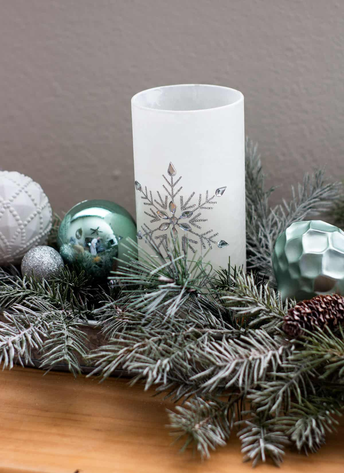 frosty christmas tiny home tour candles with greenery and ornaments on wood bench
