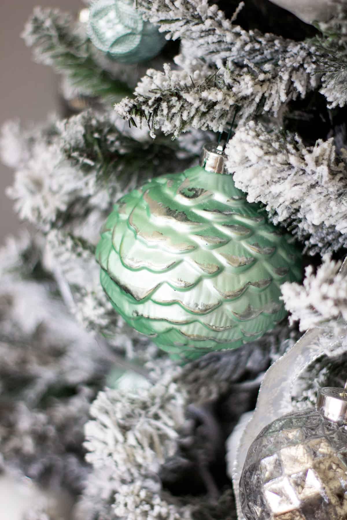 large mint ornament on flocked tree