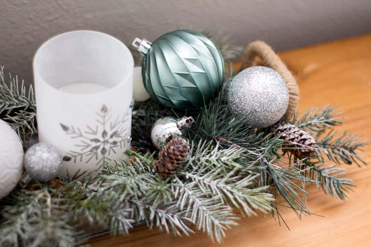 snowy greenery mint ornaments pinecones and candle on wood surface