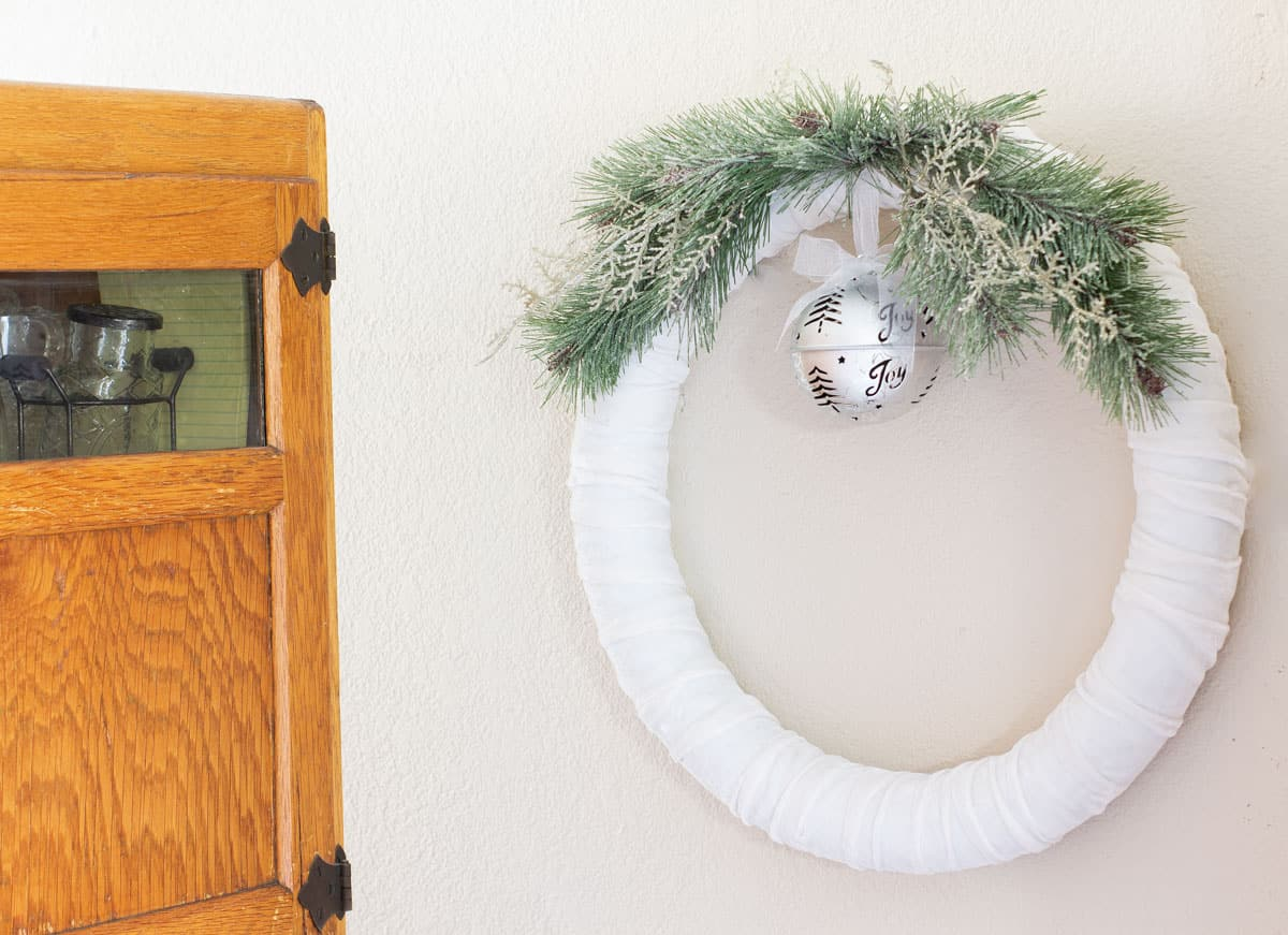 frosty christmas tiny home tour bakers cabinet with white velvet wreath greenery and jingle bell