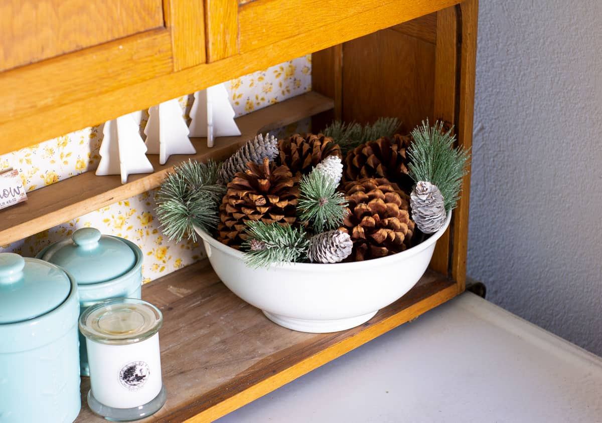 frosty christmas tiny home tour bakers cabinet with bowl of pinecones and greenery