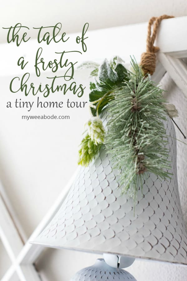 frosty christmas tiny home tour white bell with greenery hanging on wall